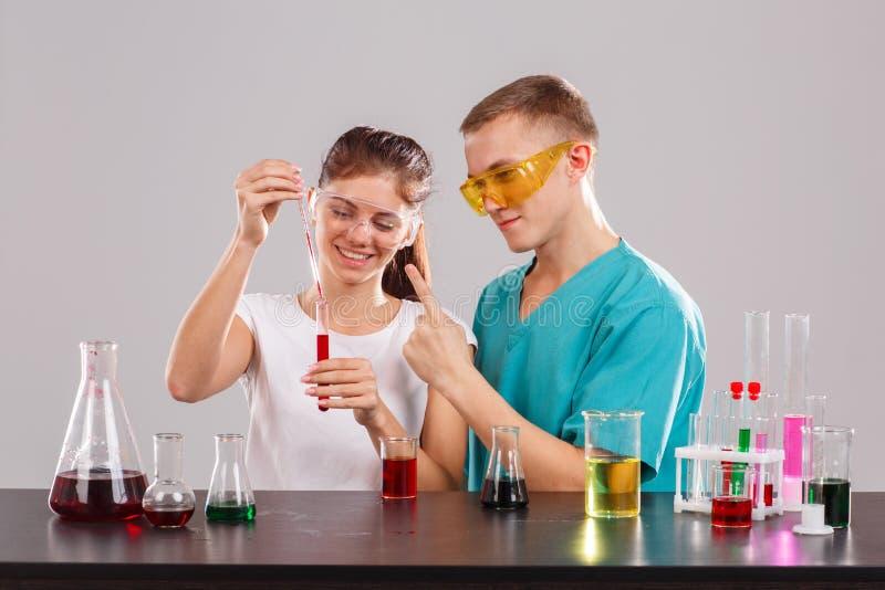 La fille verse un liquide rouge d'une pipette de mesure dans un flacon en verre, les expositions de type un doigt un photographie stock libre de droits