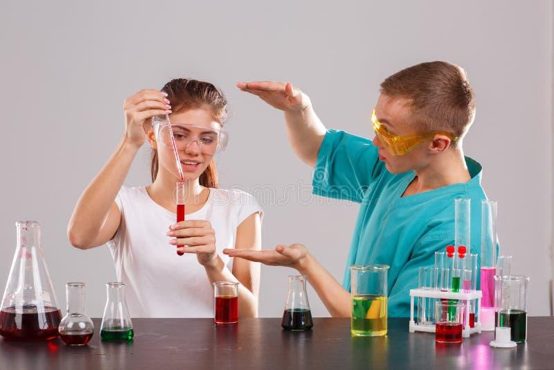 La fille verse un liquide rouge d'une pipette de mesure dans un flacon en verre, les expositions de type que la sienne remet la t photos stock