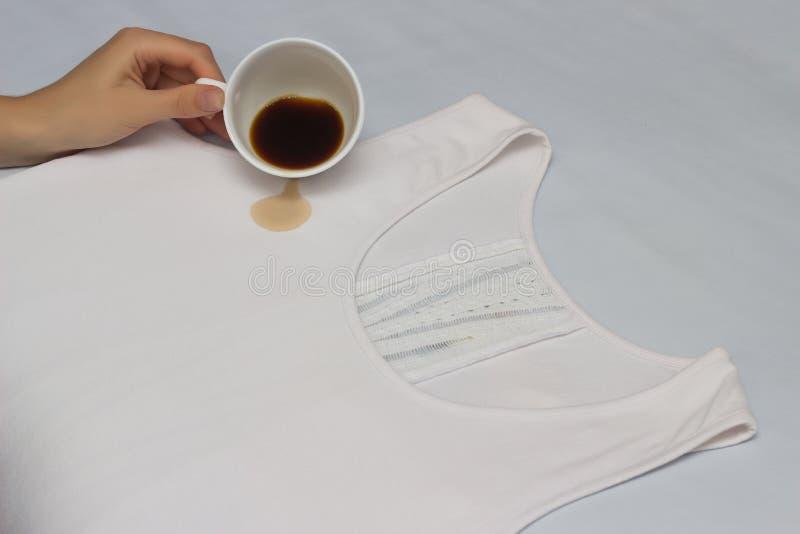 La fille verse une tasse de café sur un débardeur blanc, combattant souille sur des vêtements, vérifiant le détachant, le café et images libres de droits