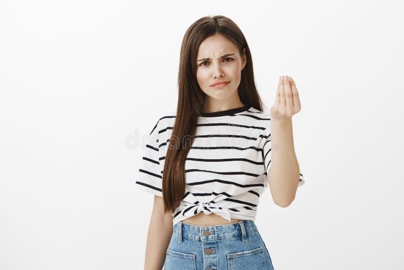 La fille veut l'acte minuscule du respect Femme européenne interrogée mécontente avec les cheveux bruns, fronçant les sourcils de image libre de droits