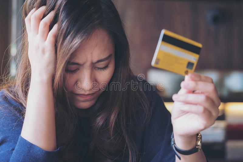 La fin asiatique de femme ses yeux tout en tenant la carte de crédit avec se sentir soumise à une contrainte et s'est cassée photo stock