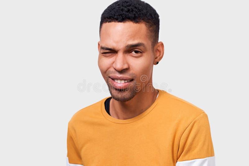 La fin d'intérieur vers le haut du portrait du jeune homme beau d'Afro-américain avec l'expression positive, clignote l'oeil et s photos stock