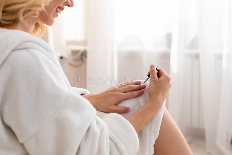 La fin d'une femme bien faite a peint ses clous pendant le matin, tout en se reposant sur le lit étant habillé dans une robe de c images stock
