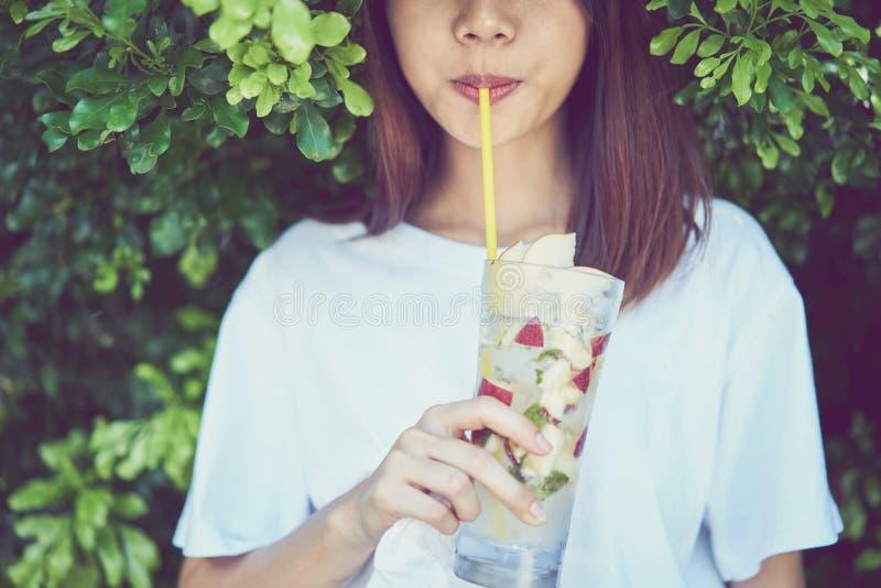 La fin de la belle détente de femme mangent du jus de fruit de boissons dans le jardin photo stock
