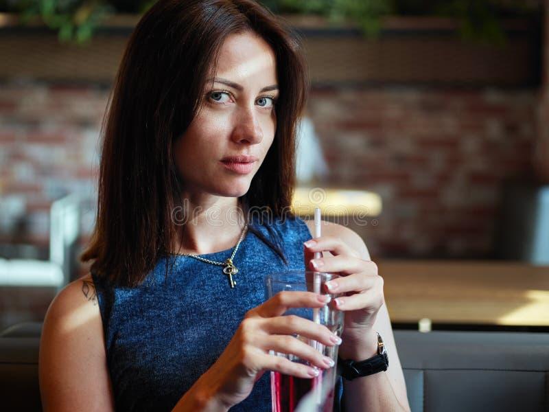 La fin de la belle femme adulte de brune dans des jeans préparent le thé de glace potable de la tasse en verre avec la paille au  images libres de droits