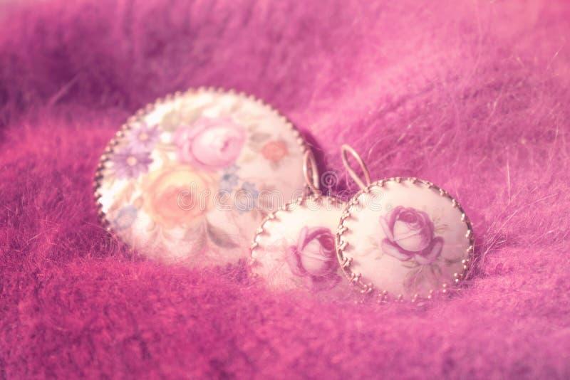 La fin de bijoux de vintage sur le rose pelucheux a tricoté le fond vieux images libres de droits