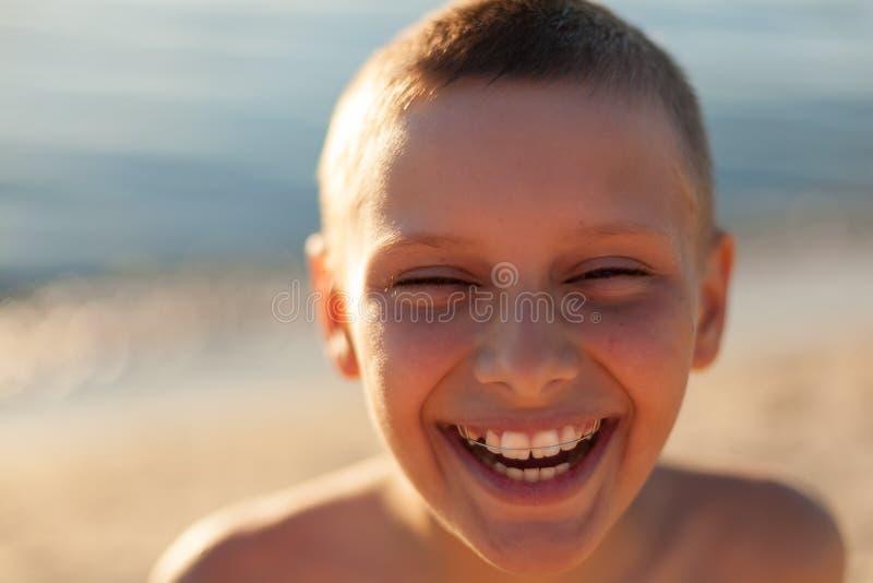 La fin de portrait de garçon d'enfant vers le haut de rire heureux de contre-jour de coucher du soleil attache des dents images stock