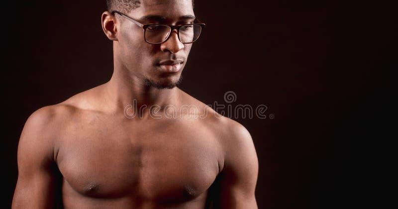 La fin de vue de côté a cultivé le portrait du mâle nacked fort d'Afro en verres photos libres de droits