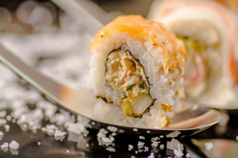 La fin du centre sélectif des sushi délicieux enroule plus d'une cuillère métallique avec de petits grains de sel servis sur le n image stock