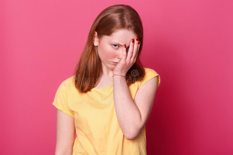 La fin du portrait haut de la jeune belle femelle d'étudiant, couvre le visage de main, étant fatigué après école, a un bon nombr image libre de droits