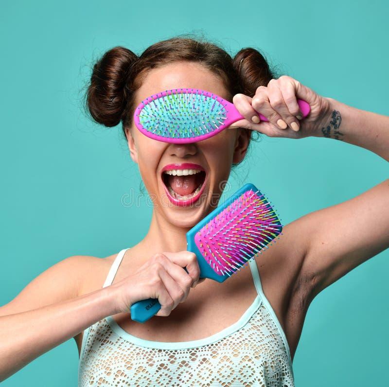 La fin heureuse de femme de brune de mode observe avec la grande brosse de cheveux bleue rose colorée photo stock