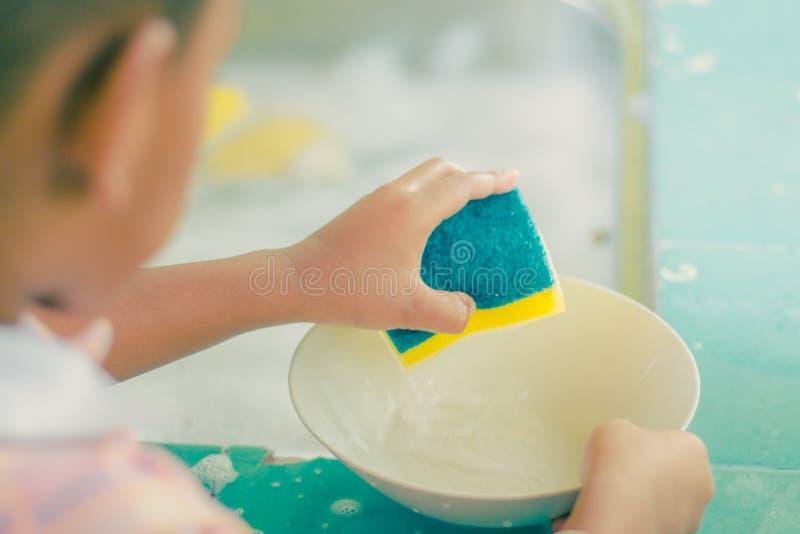 La fin jusqu'aux mains de l'étudiant de jardin d'enfants nettoie le plat photos stock