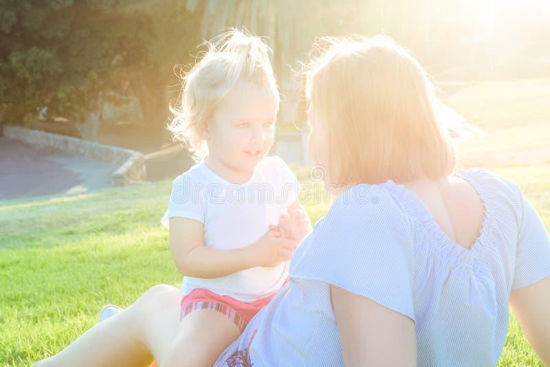 La fin vers le haut de la fille de bébé de mère et d'enfant en bas âge détendant, embrassant, riant et ont l'amusement sur le pré photographie stock
