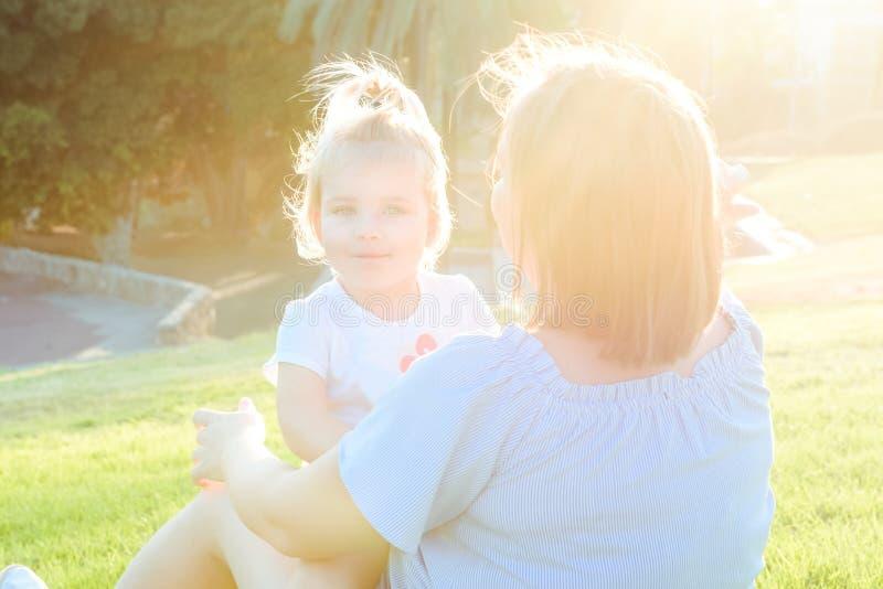 La fin vers le haut de la fille de bébé de mère et d'enfant en bas âge détendant, embrassant, riant et ont l'amusement sur le pré photo libre de droits