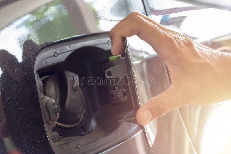 La fin vers le haut de l'homme de main ouvrent la couverture de réservoir de carburant dans la voiture image libre de droits