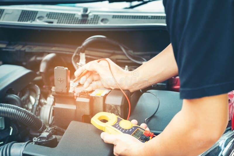 La fin vers le haut de l'outil et les hommes remettent de la réparation de voiture de mécanicien pendant l'investi image stock