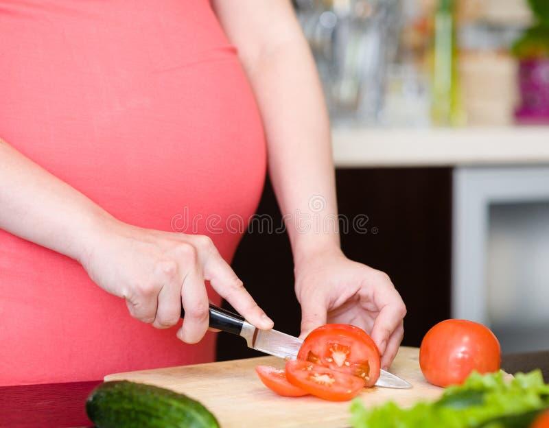 La fin vers le haut de la femme enceinte avec le couteau sur la cuisine coupe la tomate image libre de droits