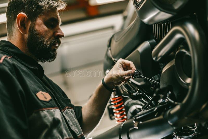 La fin vers le haut de la vue inférieure du mécanicien vérifie le niveau d'huile dans la moto photo stock