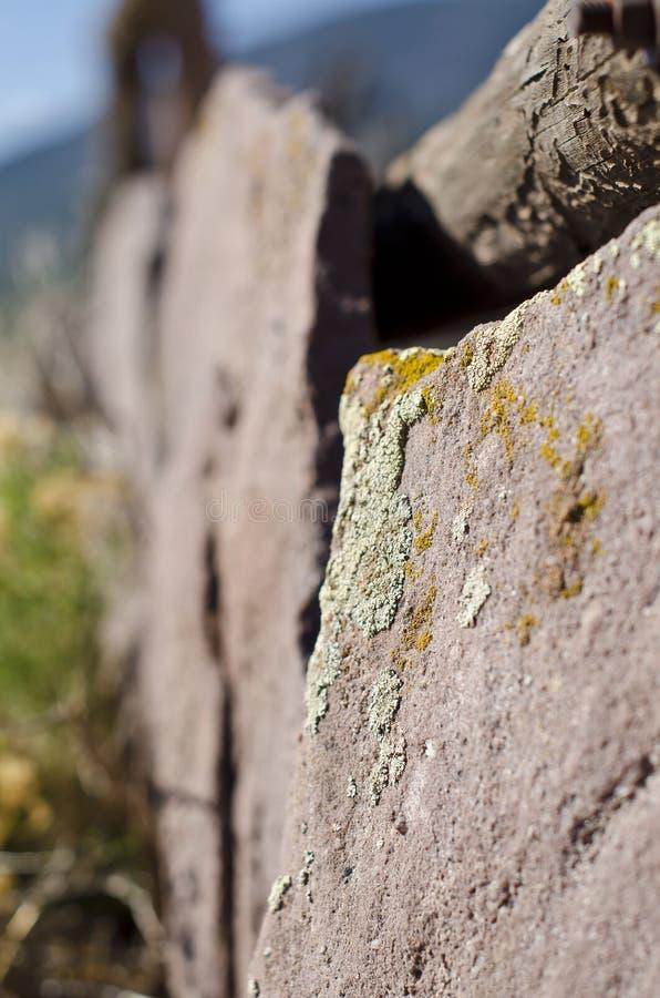 La fin vers le haut de la longue vue de la ligne de barrière rouge de roche images stock