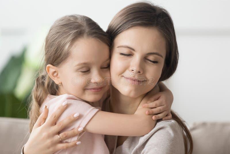 La fin vers le haut de la mère affectueuse caressent peu de fille mignonne photos stock