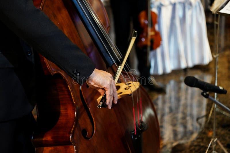 La fin vers le haut de la main du musicien joue la double basse dans l'événement d'intérieur image stock
