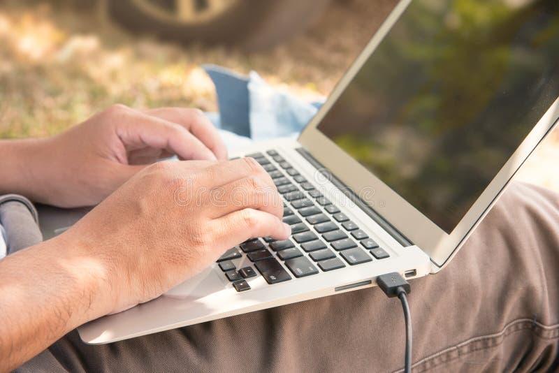 La fin vers le haut de la main du ` s de l'homme utilisent leurs ordinateurs portables sur les jambes photographie stock libre de droits