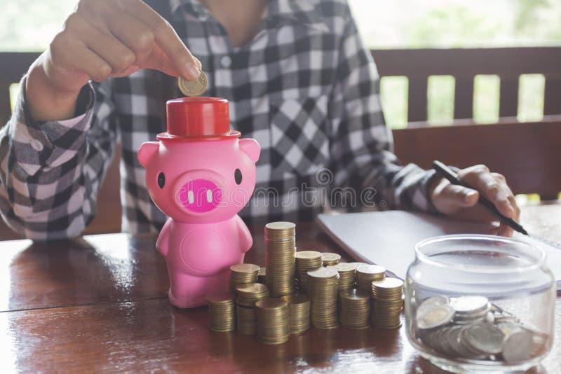 La fin vers le haut de la main femelle mettant la pièce de monnaie dans la tirelire, épargnent l'argent pour l'avenir photo libre de droits