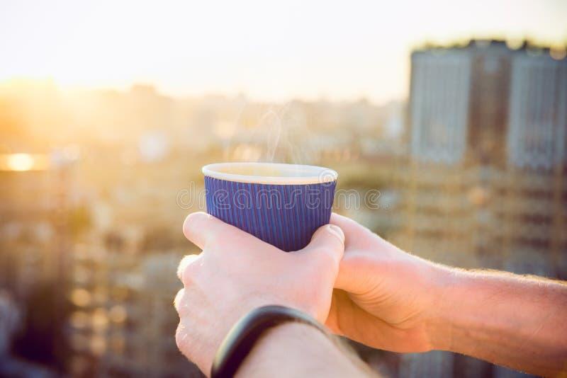 La fin vers le haut de se tenir de mains du ` s de l'homme emportent la tasse de papier avec la boisson chaude de matin - café ou photos libres de droits