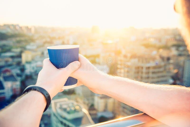 La fin vers le haut de se tenir de mains du ` s de l'homme emportent la tasse de papier avec la boisson chaude de matin - café ou photographie stock