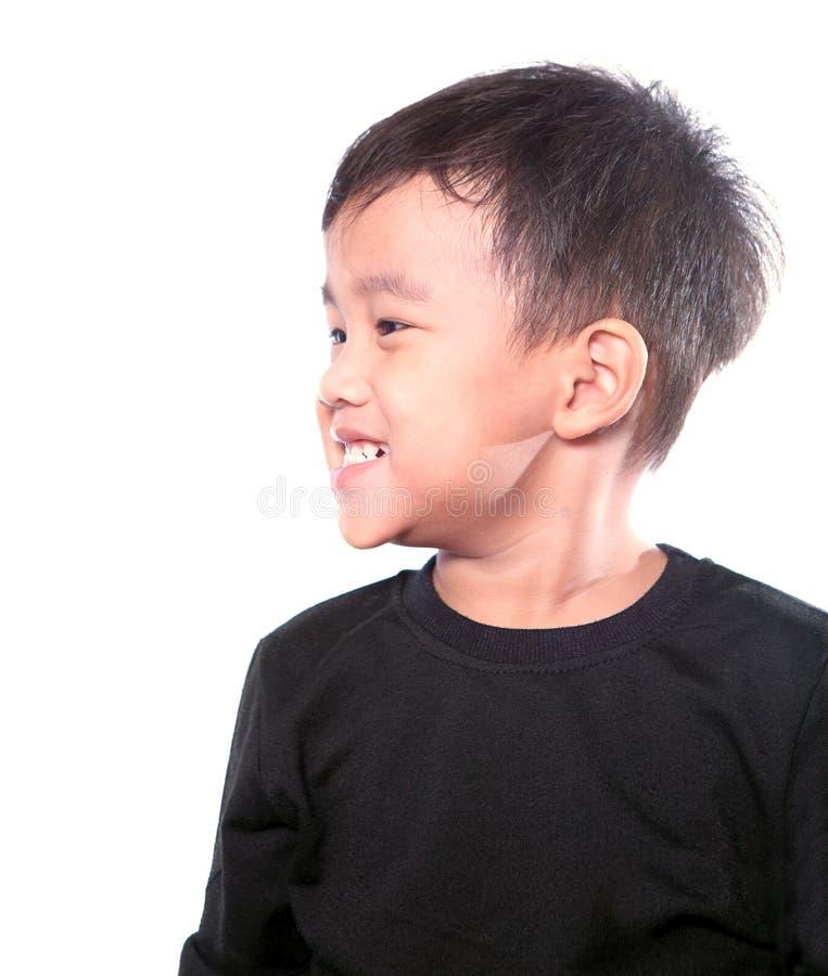 La fin vers le haut de la tête latérale tirée du visage de sourire toothy d'enfants asiatiques est image libre de droits