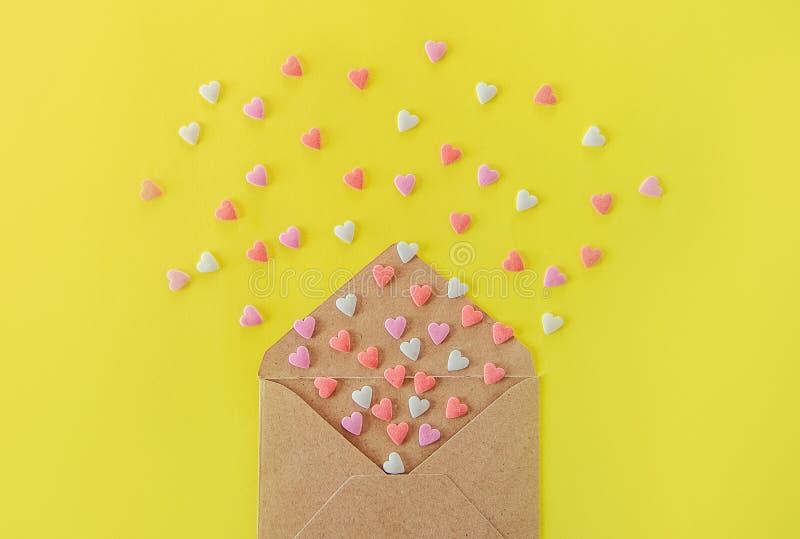 La fin vers le haut des coeurs multicolores de sucrerie de sucre de bonbons volent hors de l'enveloppe de papier de métier sur le photo libre de droits