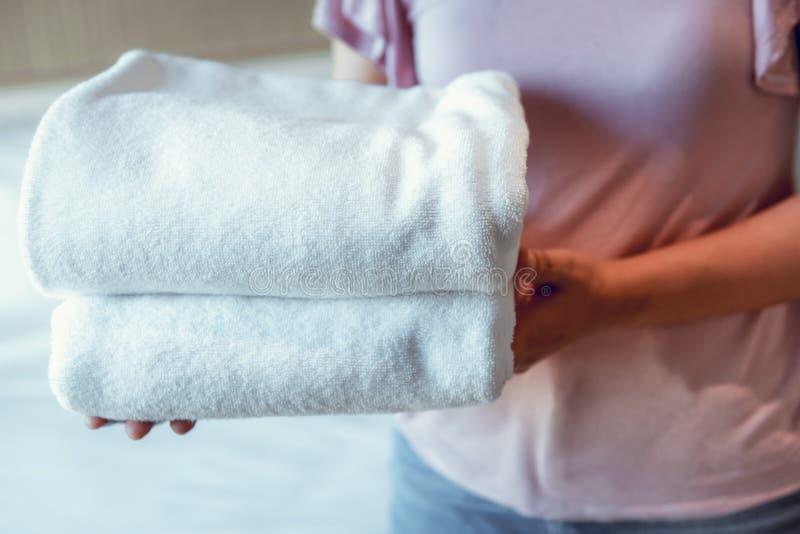 La fin vers le haut des mains de femme tient la pile des serviettes dans la chambre à coucher Concept de massage de station therm photographie stock libre de droits