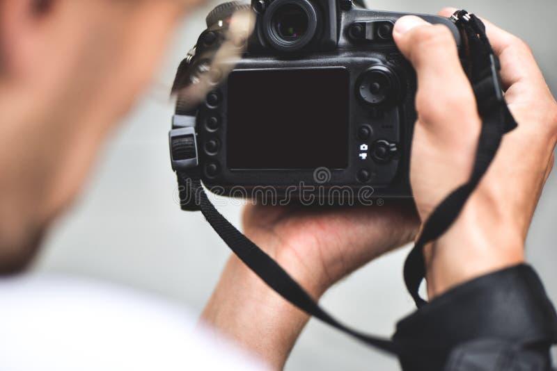 La fin vers le haut des mains masculines tiennent la caméra professionnelle et font une photo images stock