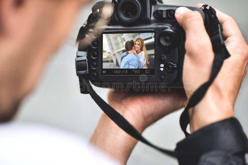 La fin vers le haut des mains masculines tiennent la caméra professionnelle et font une photo photo stock