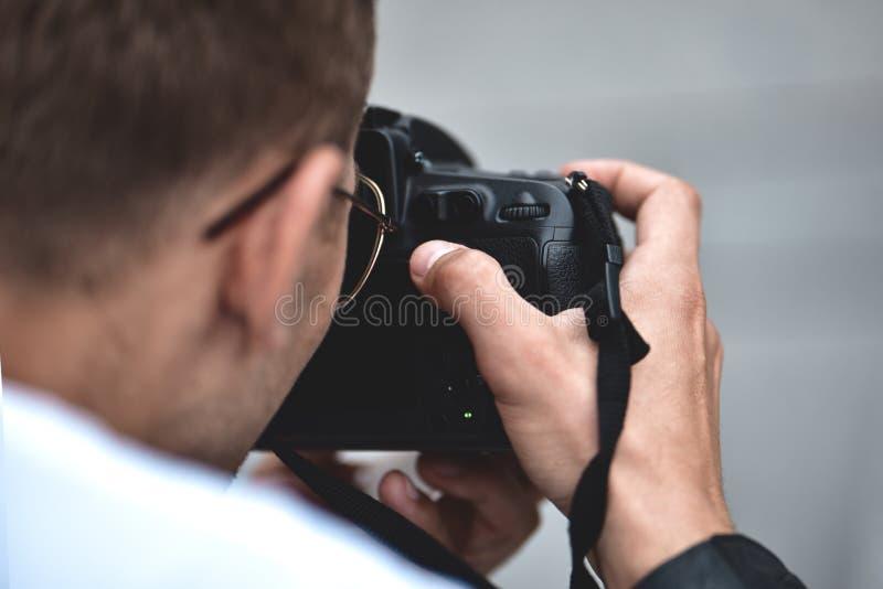 La fin vers le haut des mains masculines tiennent la cam?ra professionnelle et font une photo image stock