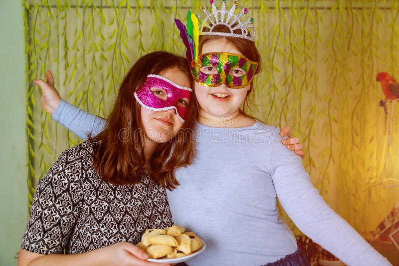 La fin vers le haut du bonheur de l'amusement et les expressions heureuses dans les masques de fête de carnaval avec hamantaschen photographie stock
