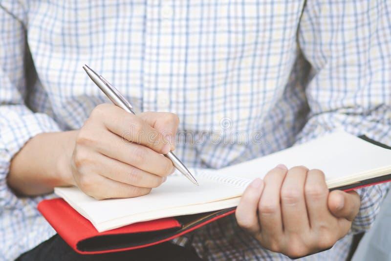 La fin vers le haut du jeune homme de main se reposent utilisant le stylo écrivant le bloc-notes record de conférence photographie stock