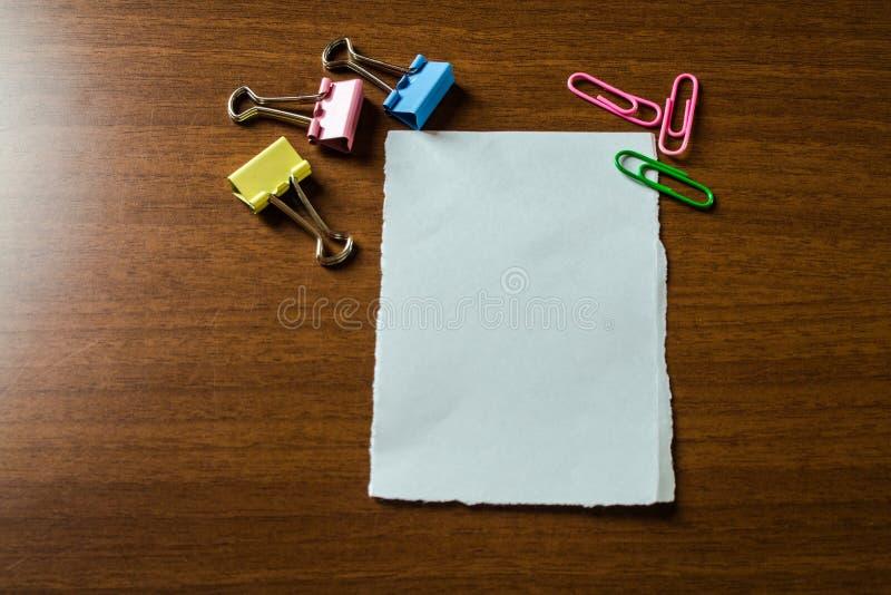La fin vers le haut du papier stationnaire de blanc de vue a mis trois agrafes colorées et table en bois menteuse de reliures Acc photo stock