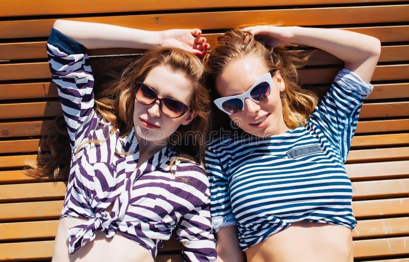 La fin vers le haut du portrait d'été de mode de vie de deux amies décontractés et obtenants les prennent un bain de soleil, s'ét image stock