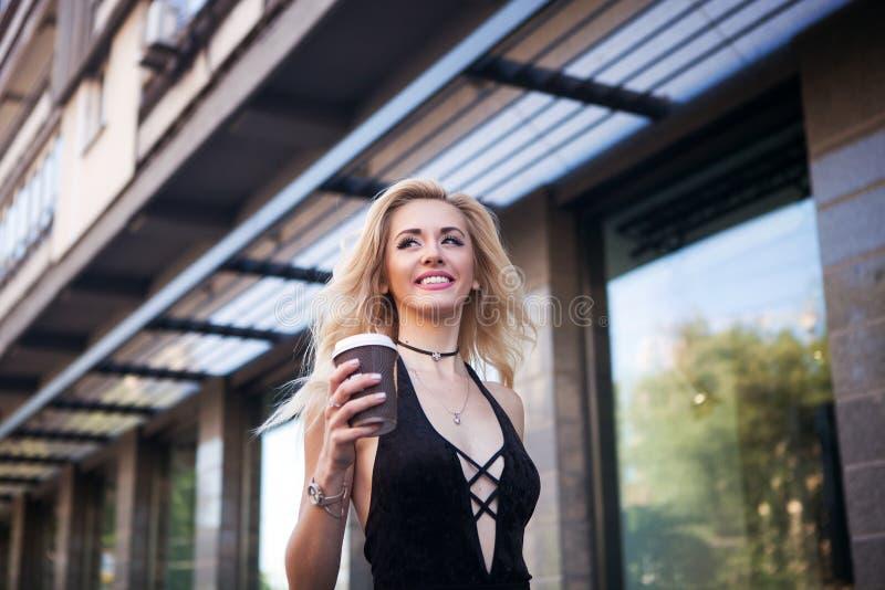 La fin vers le haut du portrait de la femme riante heureuse dans un équipement occasionnel marche dans la ville La belle blonde s image libre de droits