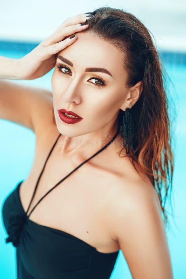 La fin vers le haut du portrait de la femme sexy élégante dans le bikini noir sur le beau corps pose près de la piscine en villa  images libres de droits