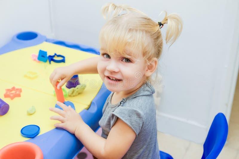 La fin vers le haut du portrait de la petite fille mignonne d'enfant en bas âge moule de la pâte à modeler sur la table dans la c photo stock