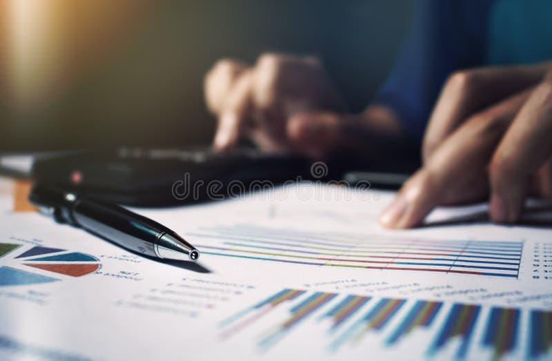 La fin vers le haut du stylo sur des écritures et la main de femme calculent des finances photographie stock