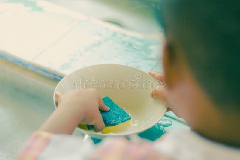 La fine fino alle mani dello studente di asilo sta pulendo il piatto immagine stock