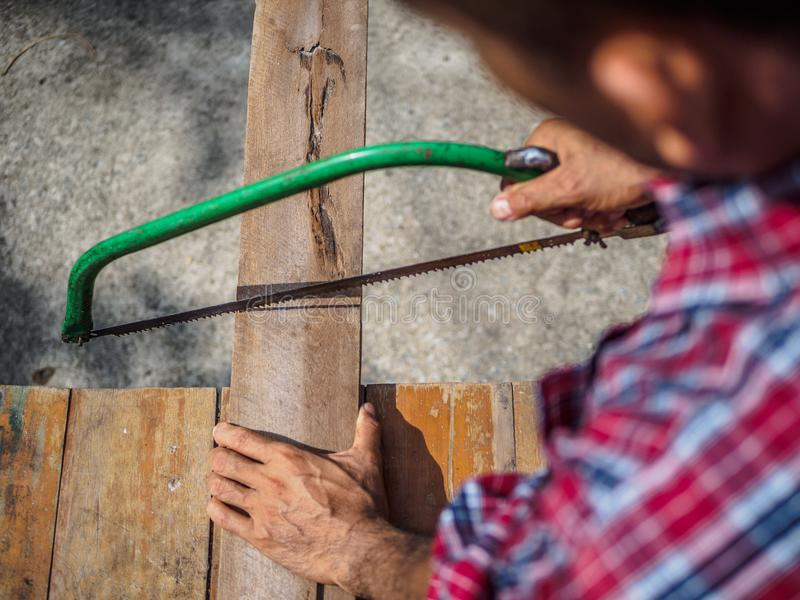 La fine su del carpentiere che sega un bordo con un legno della mano ha visto Profe fotografia stock libera da diritti