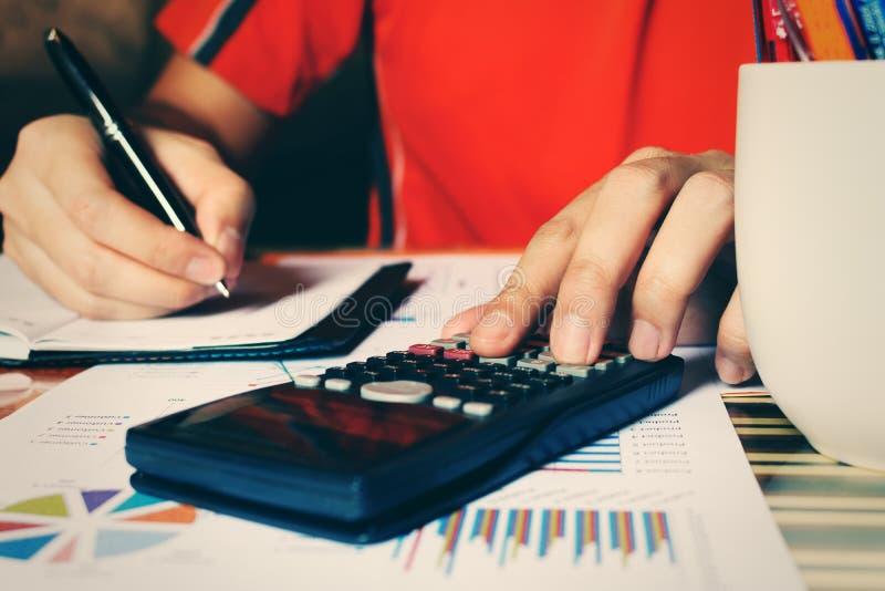 La fine su dell'uomo della mano calcola le spese e di fabbricazione nota a casa immagine stock