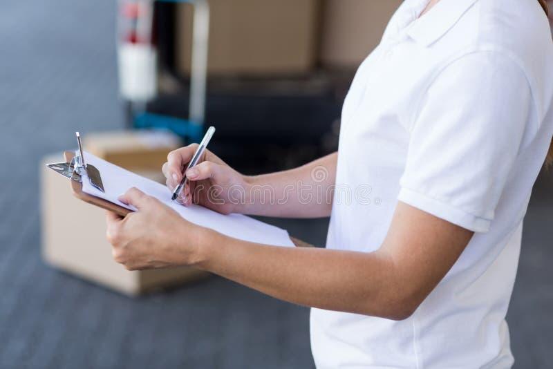 La fine su della donna della consegna sta scrivendo su una lavagna per appunti fotografia stock