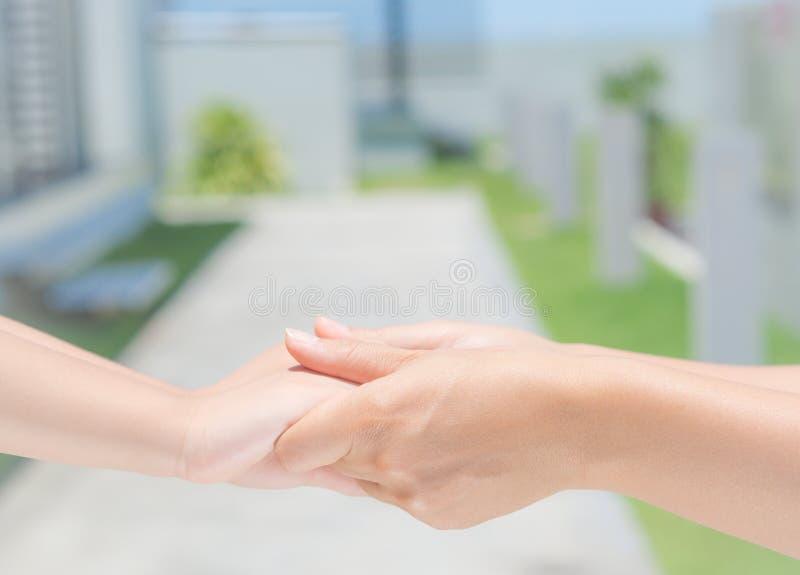 La fine su della donna tiene la mano di un bambino adorabile immagine stock