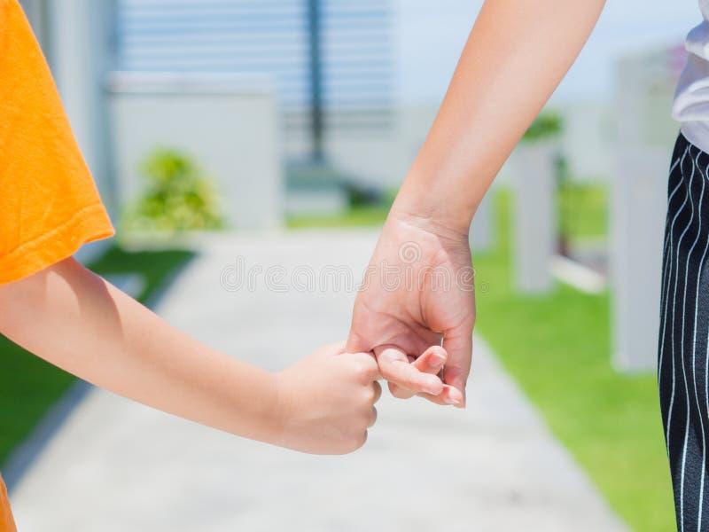 La fine su della donna tiene la mano di un bambino adorabile fotografia stock libera da diritti