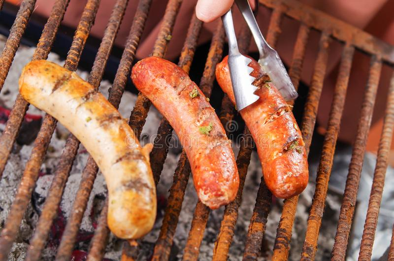 La fine su della mano della donna s che giudica tenaglie che girano le salsiccie grigliare sul barbecue griglia BBQ Salsiccie bav fotografia stock libera da diritti